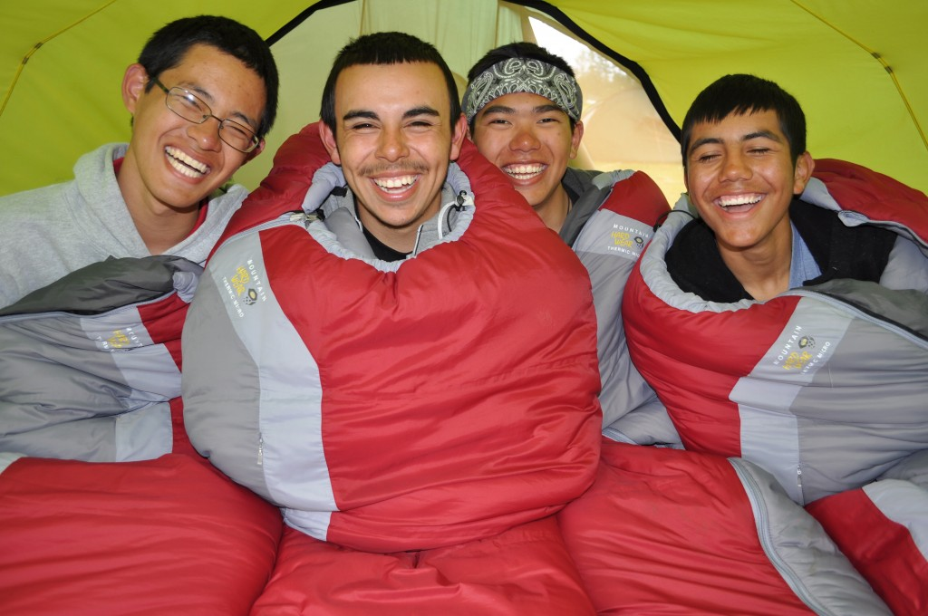 Four smiling teens in sleeping bags