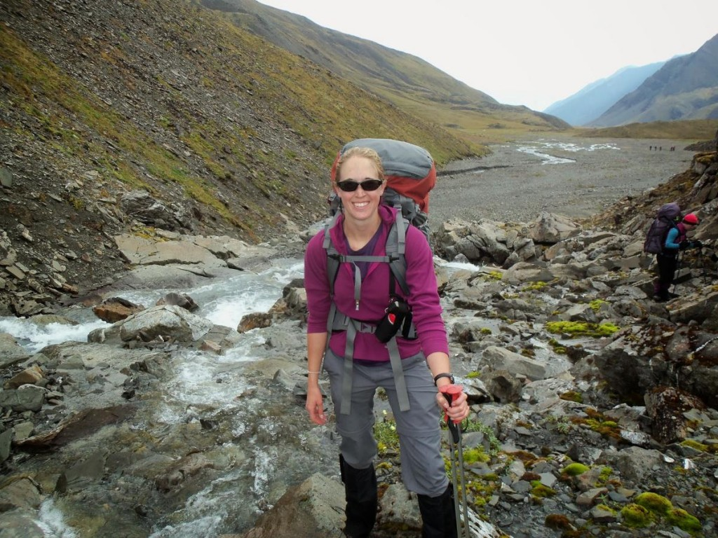 Smiling backpacker standing beside a rocky stream