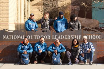 Expedition Denali pose in front of NOLS World Headquarter sign