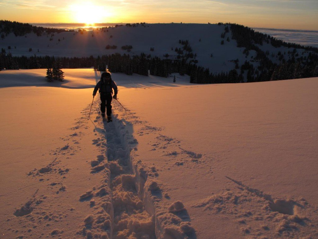 Ski touring across a snowfield at sunset