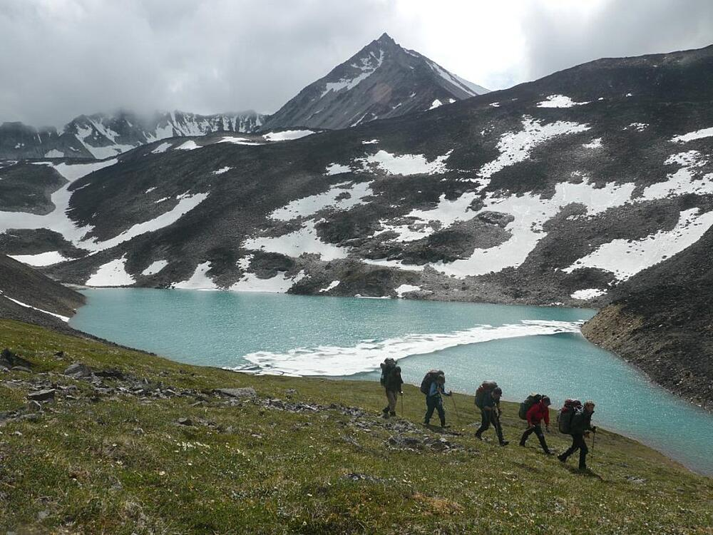 Group hiking along a lake in Alaska