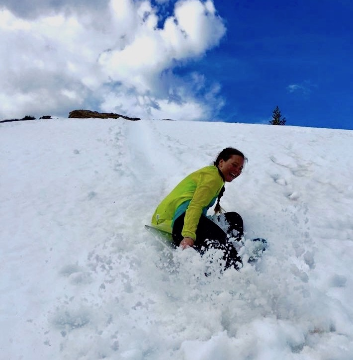 smiling person sleds down a hill in a spray of snow