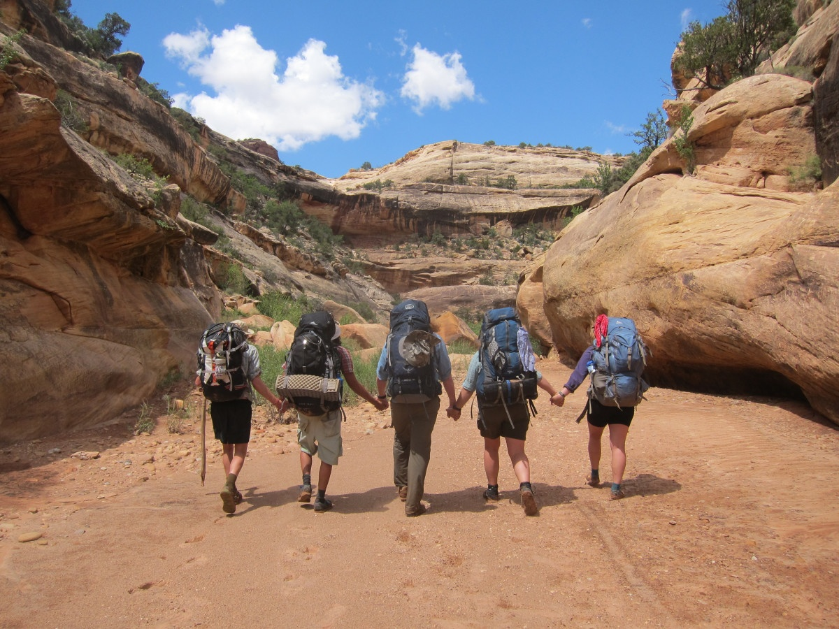 A group hikes through canyons while holding hands