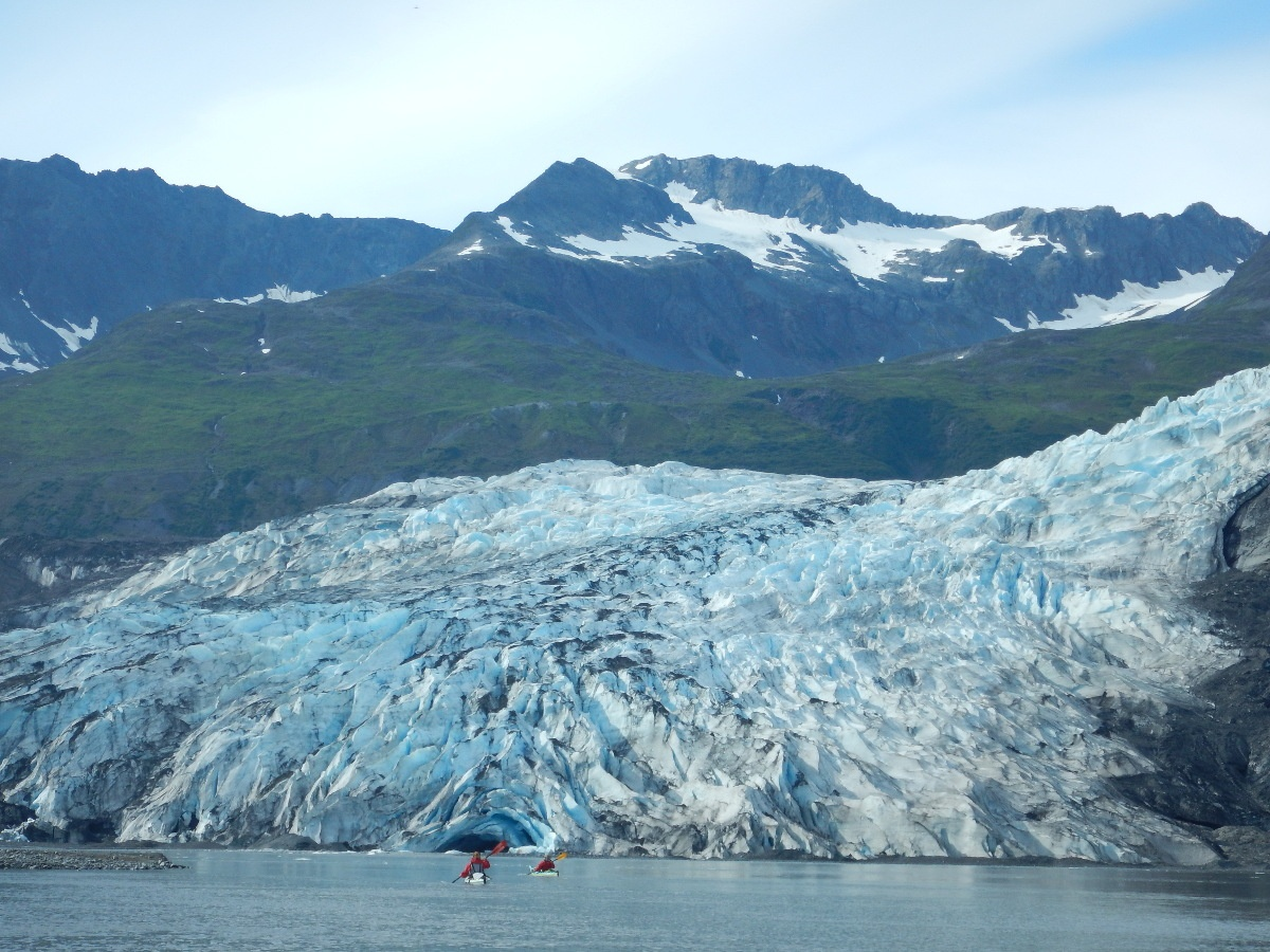 Two sea kayakers paddle on the coast with large glacier and green coastline in the background