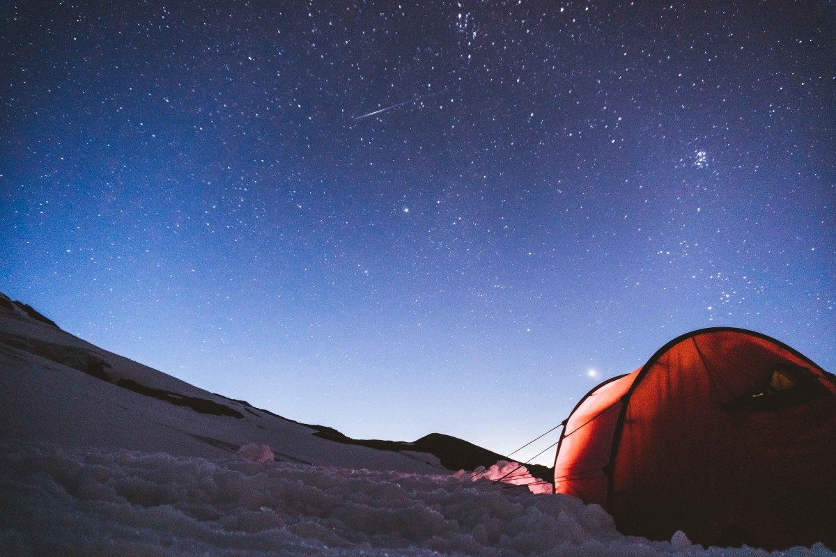 A tent at night in the snow with bright stars filling the sky