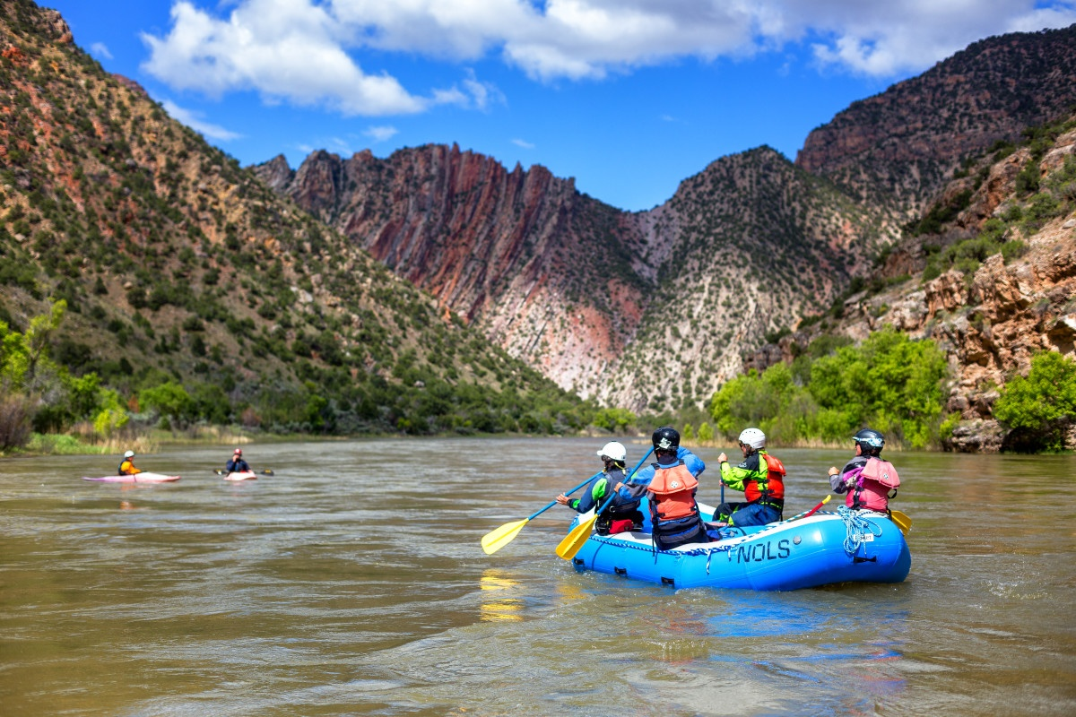 Group paddling a raft on a river