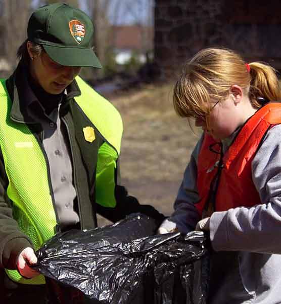 Park Service ranger and child wearing red vest and glasses hold trash bag together