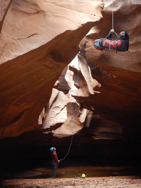 Lowering backpack into a slot canyon