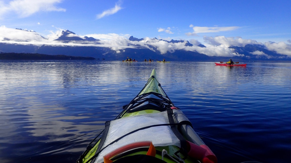 Sea kayak with other group members and mountains in the background