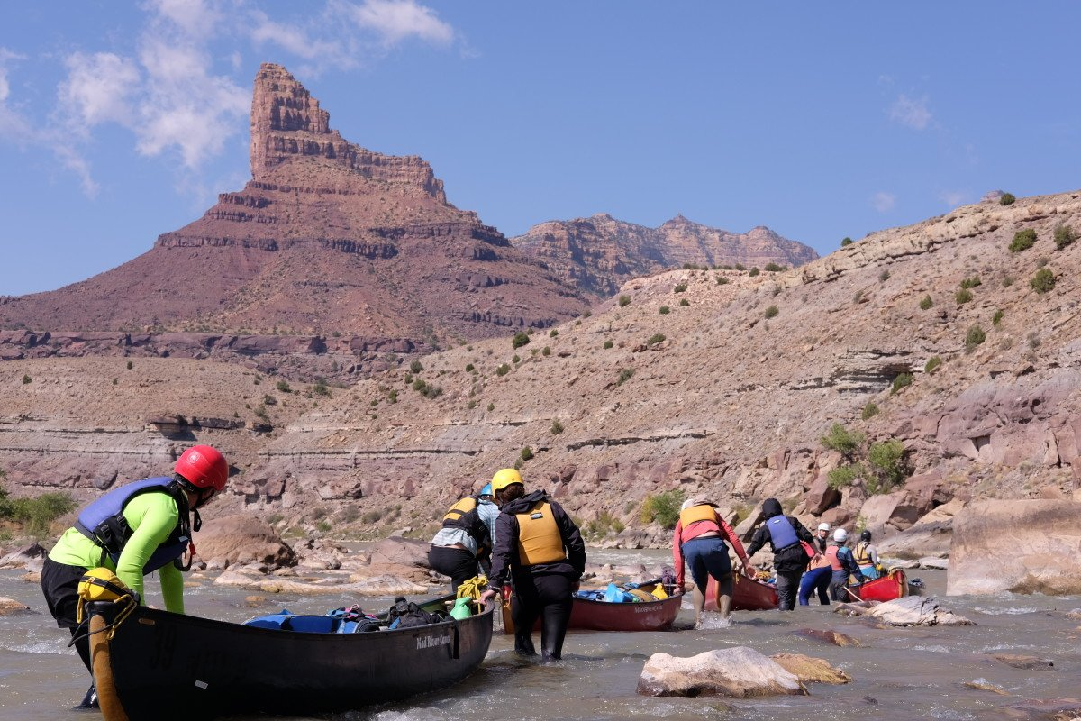 A group of people walks canoes through a rapid on a river in the desert