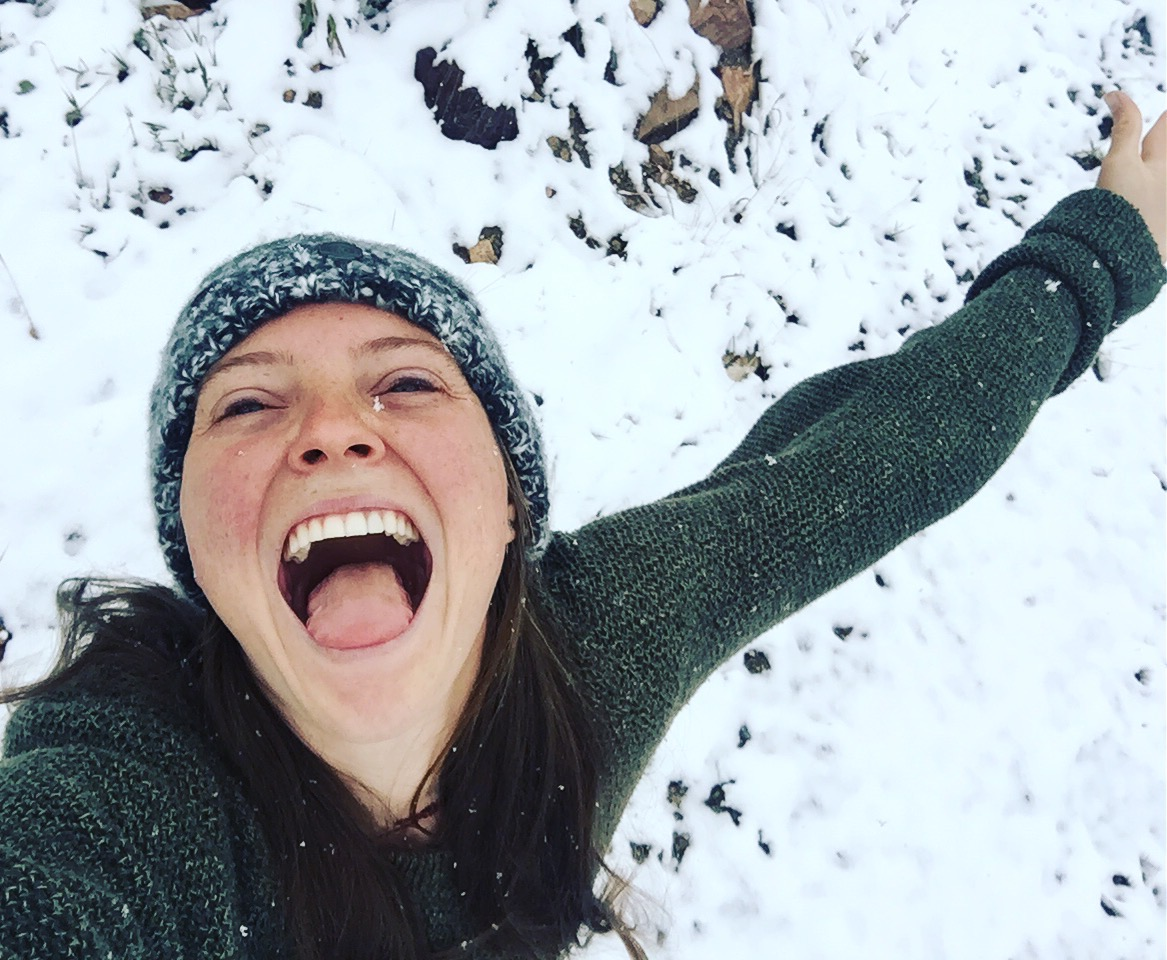 smiling person tries to catch snowflakes on her tongue
