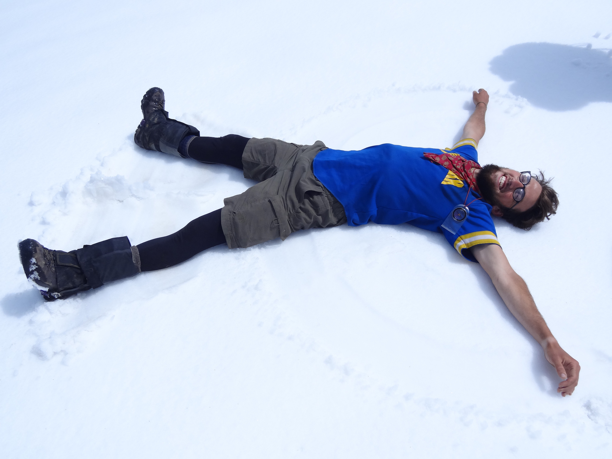 Smiling NOLS participant makes a snow angel