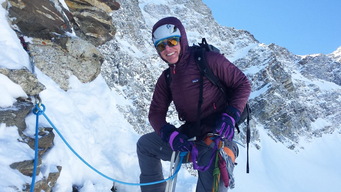 Jaime Musnicki poses wearing a jacket and climbing harness and tied into climbing protection on a snowy route