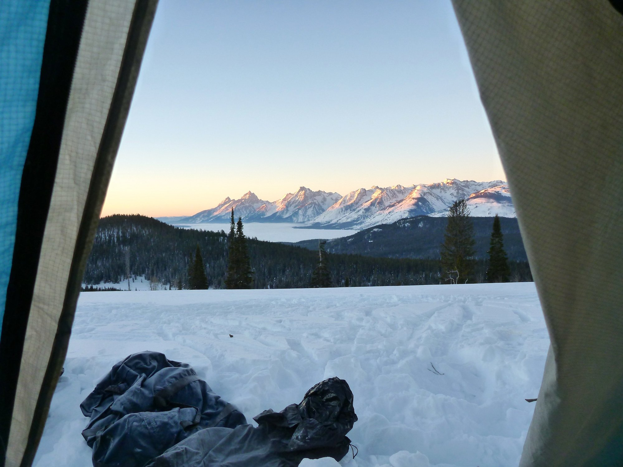 snow-covered mountain range at sunrise seen from a tent on a NOLS winter course