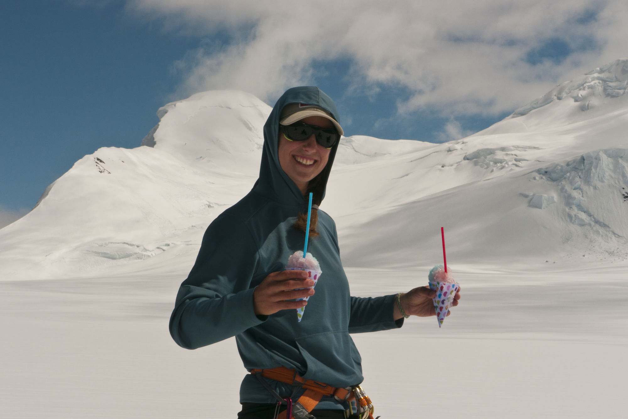smiling NOLS participant holds a snow cone in each hand  with snowy mountains in the background