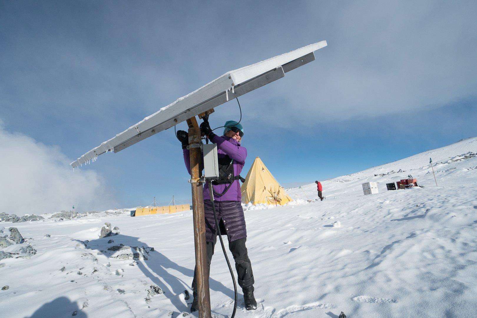 Woman repairs solar panel on snowfield