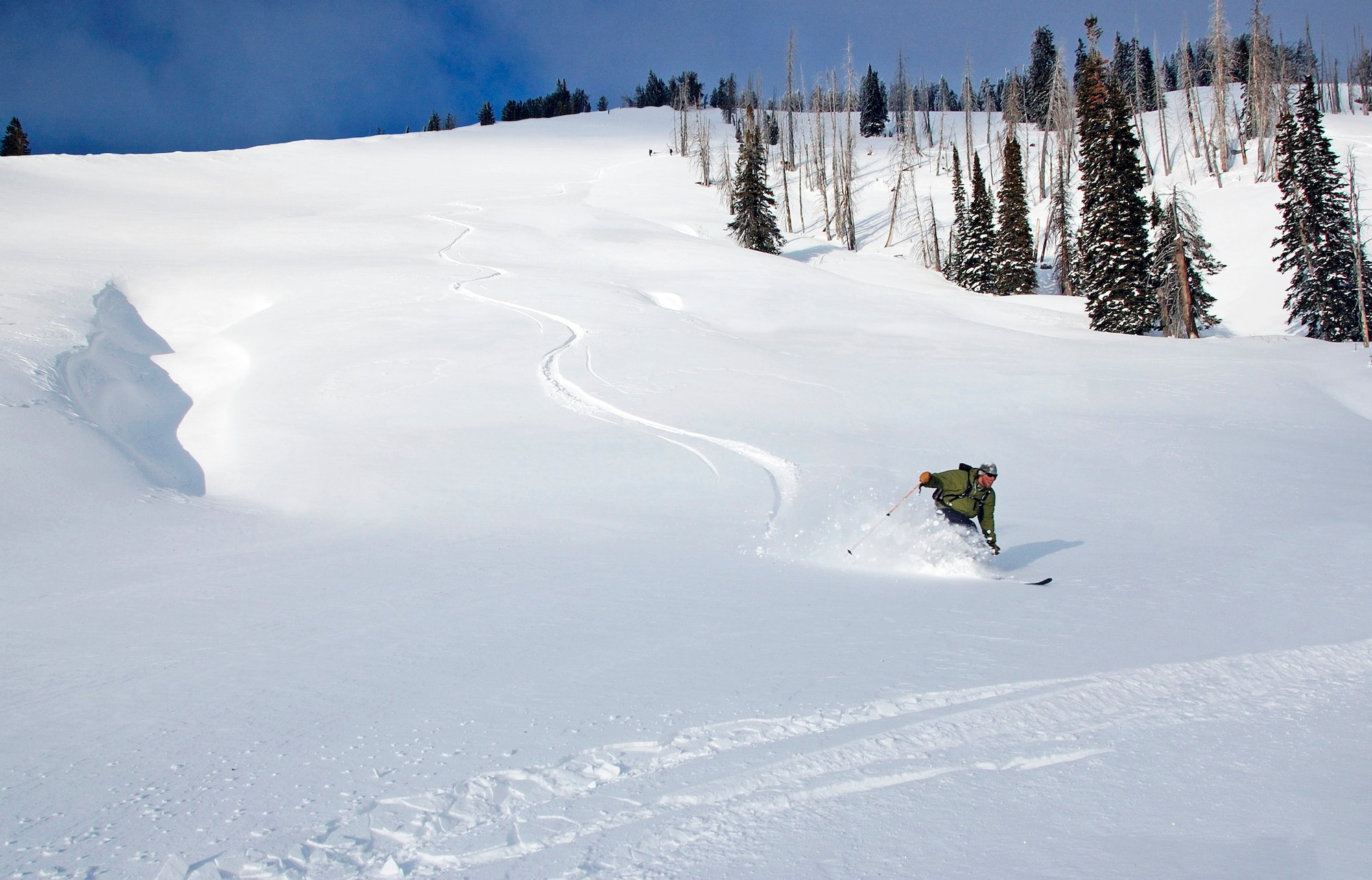 NOLS participant backcountry skis down a slope in a spray of powder