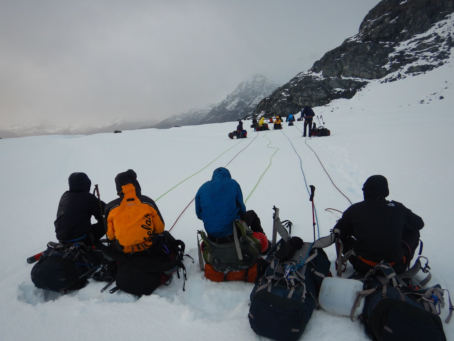 Four rope teams take a break on a glacier covered in snow