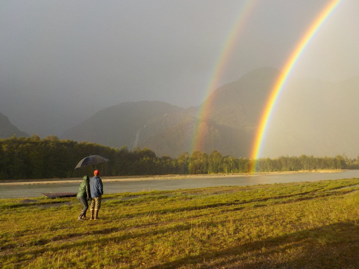 Two people with an umbrella watch two rainbows in the distance arc over a river
