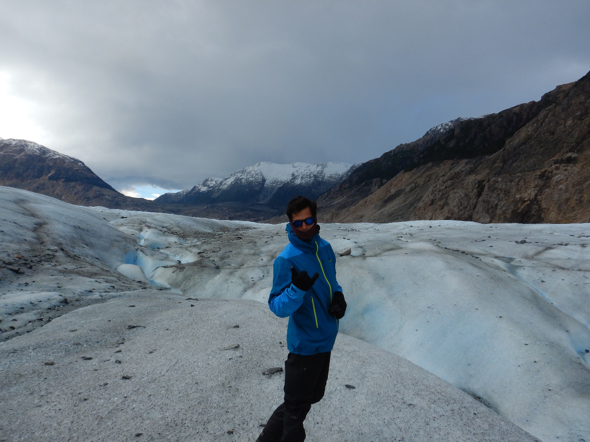 Person posing and looking at the camera standing on a glacier