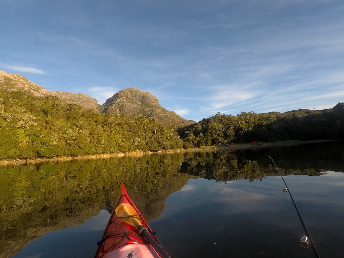 Picture taken from a sea kayak with a fishing rod and hills in the background