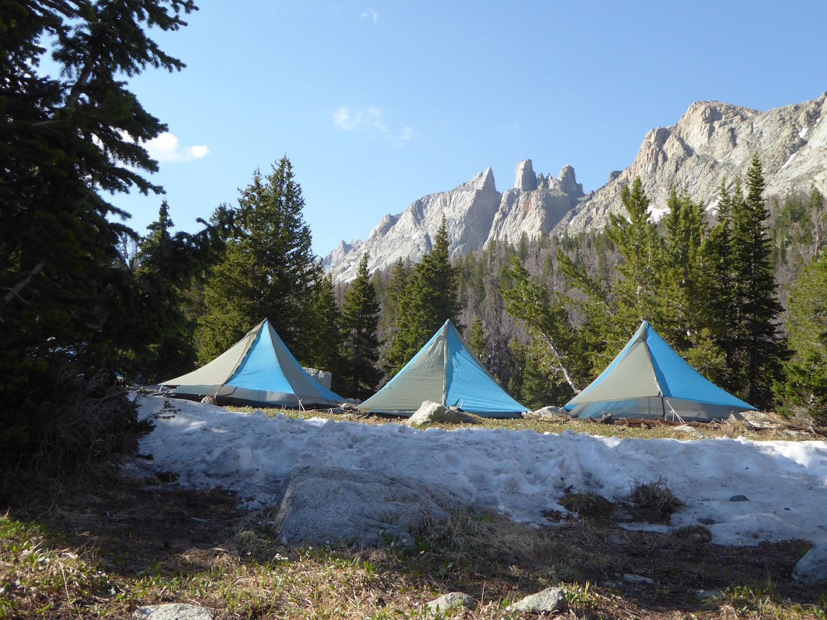 Three NOLS tents set up in a grassy clearing surrounded by trees and mountains