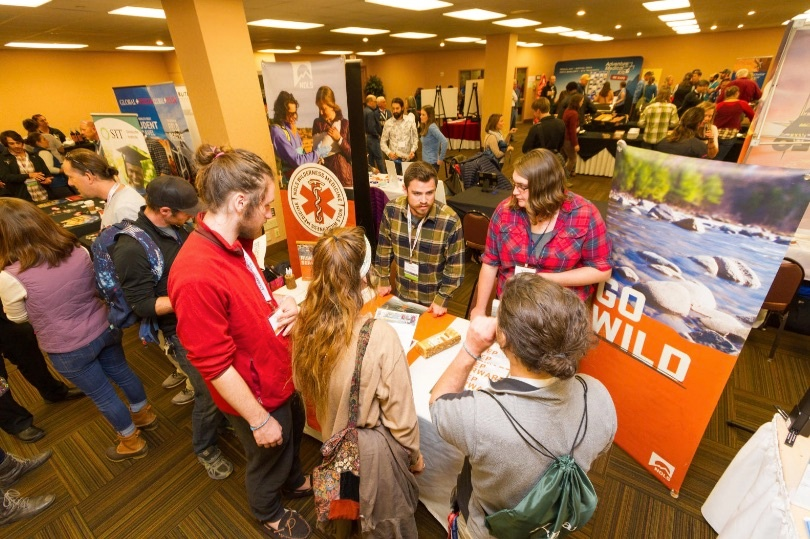 Group of people standing around a table talking with NOLS posters in the background