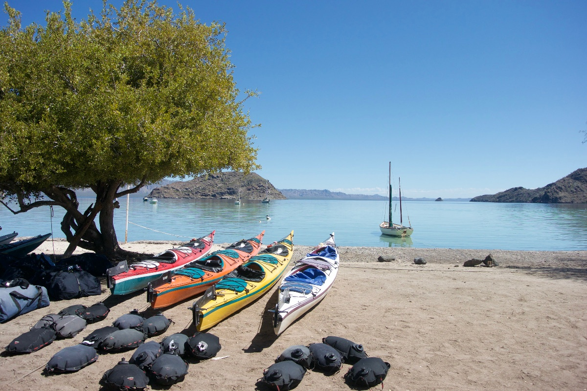 Boats on the shore with full water bags at the beginning of the trip