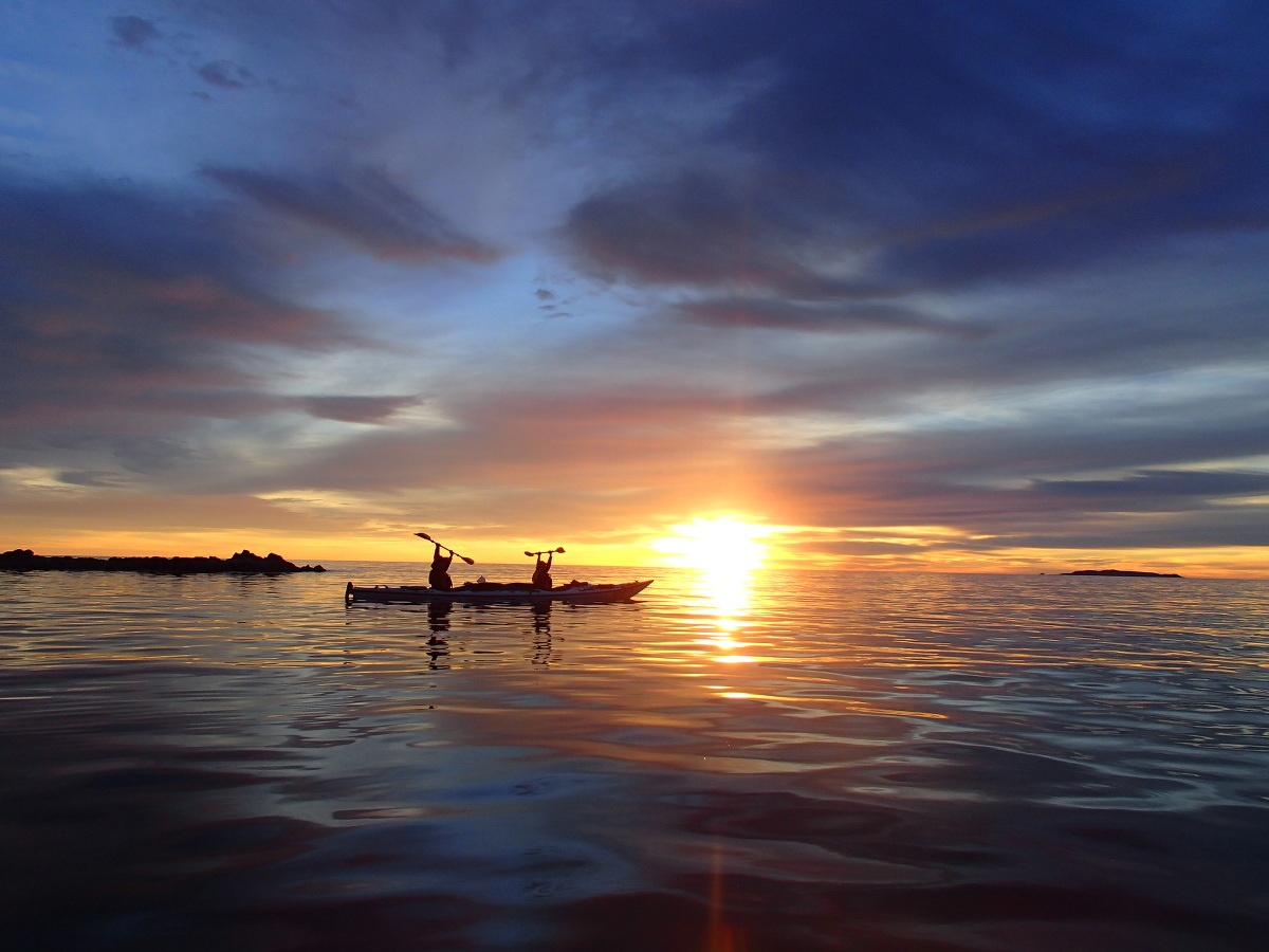 Two people in a tandem kayak raise paddles with the sunrise behind them while floating on the ocean.