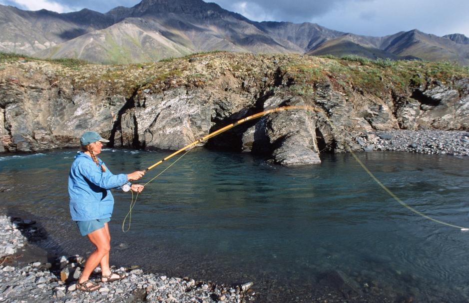 NOLS participant fishing on a rocky shore in Alaska