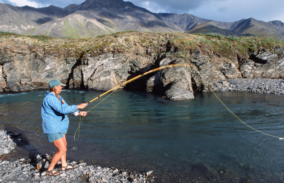 NOLS participant fishing on a rocky shore in Alaska