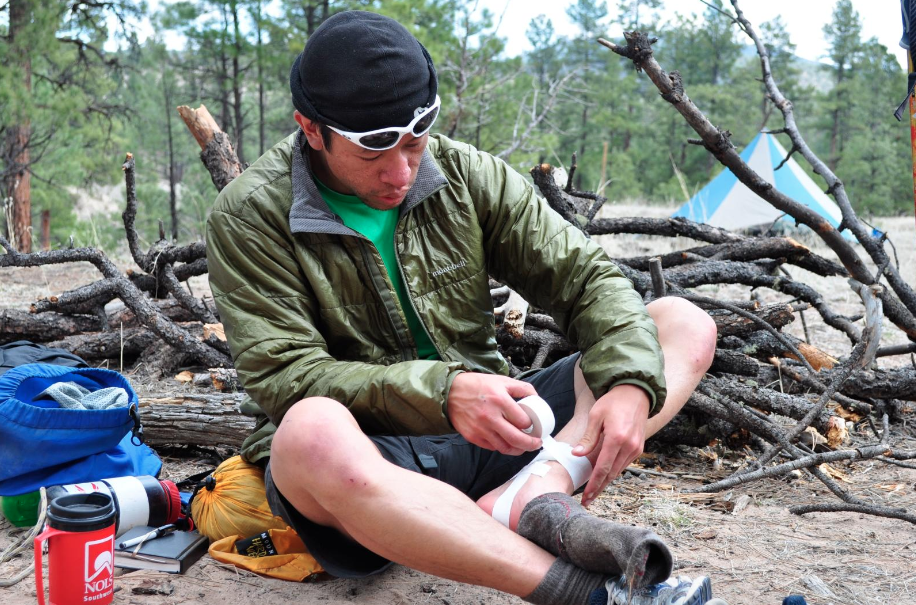 Man sitting in camp and taping his ankle