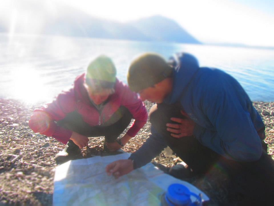 Two students crouch as they read a map on the shore of a body of water