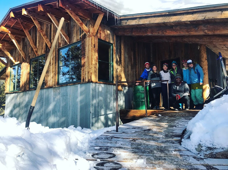 A group smiles in a mountain lodge