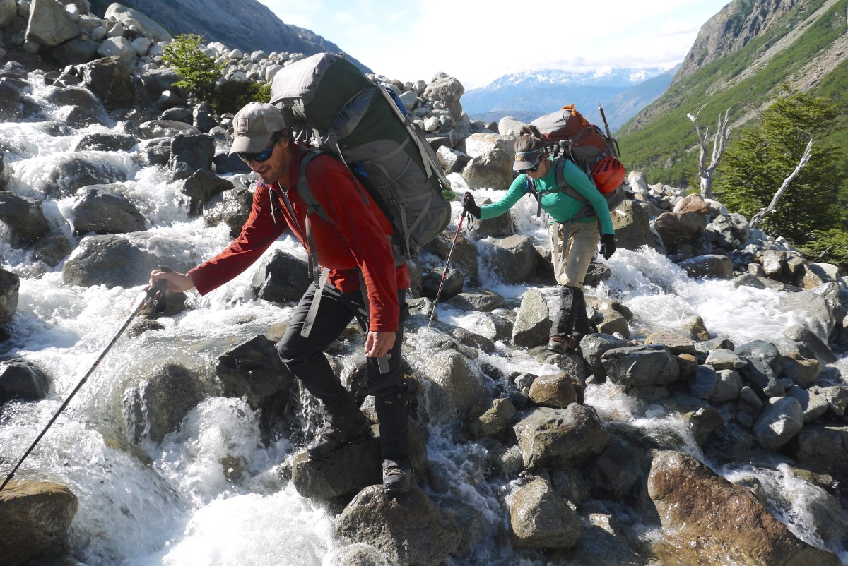Two backpackers cross a river with large rocks