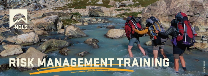 Backpackers crossing a river using risk management practices
