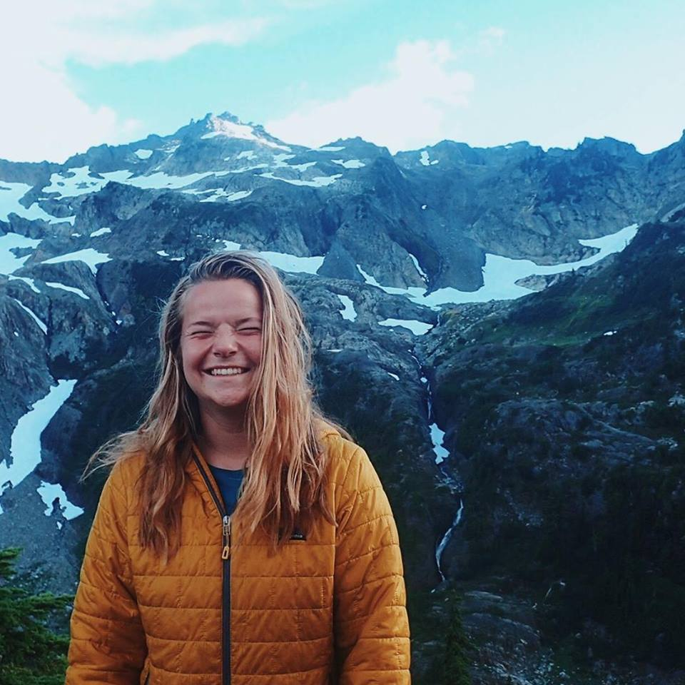 smiling NOLS backpacking student surrounded by mountains with patchy snow in the Pacific Northwest
