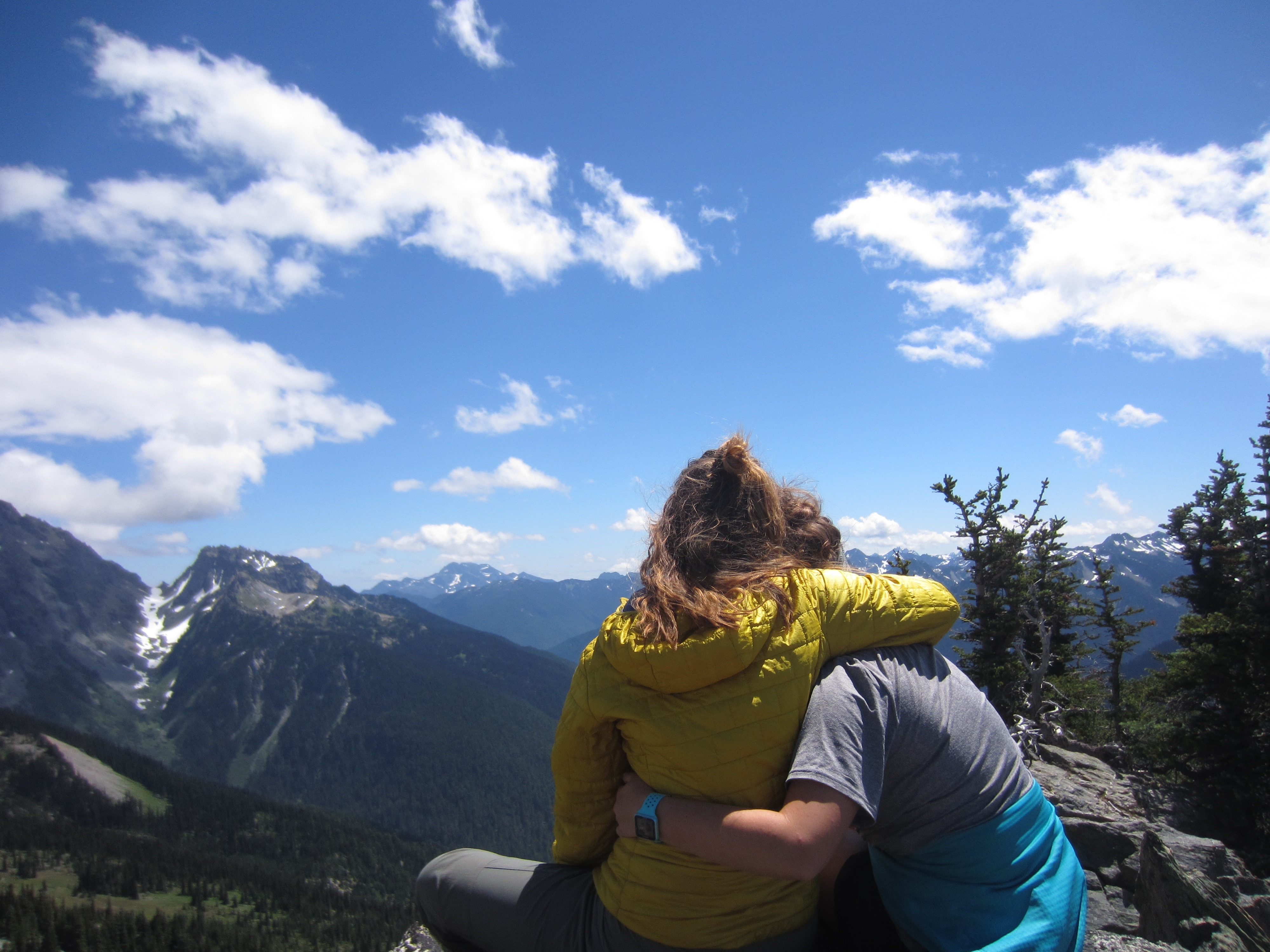 two NOLS students put their arms around each other and celebrate summiting a peak in the Pacific Northwest