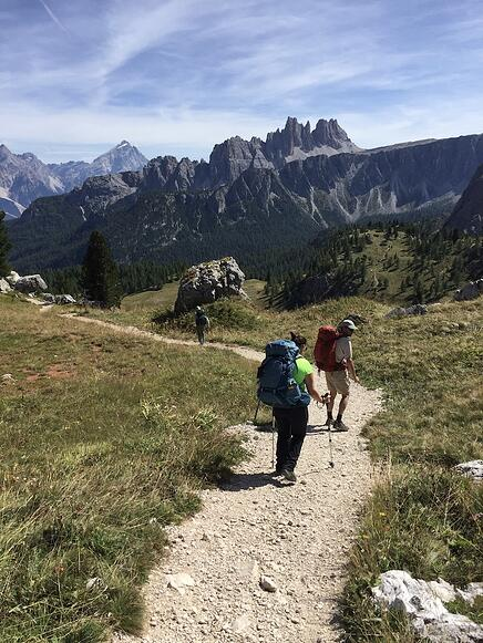 Group of hikers on thrail in the mountains with craggy peaks behind