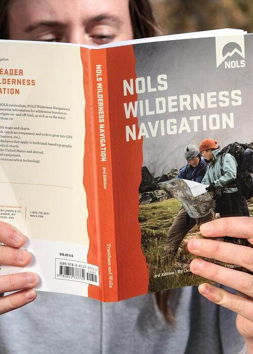 person holds NOLS Wilderness Navigation book