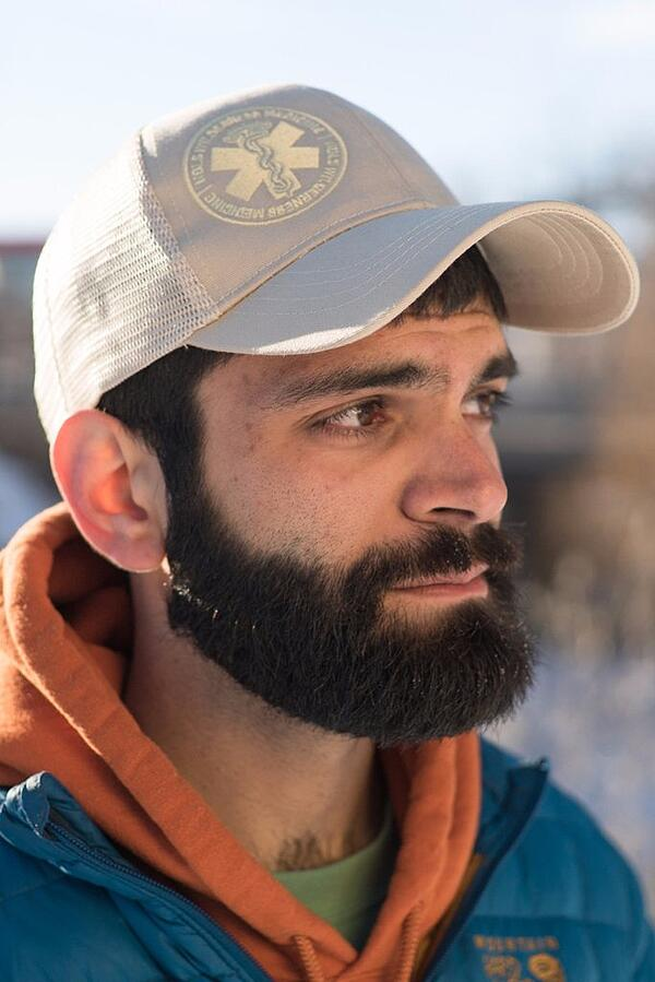 Person with beard wearing NOLS Wilderness Medicine hat