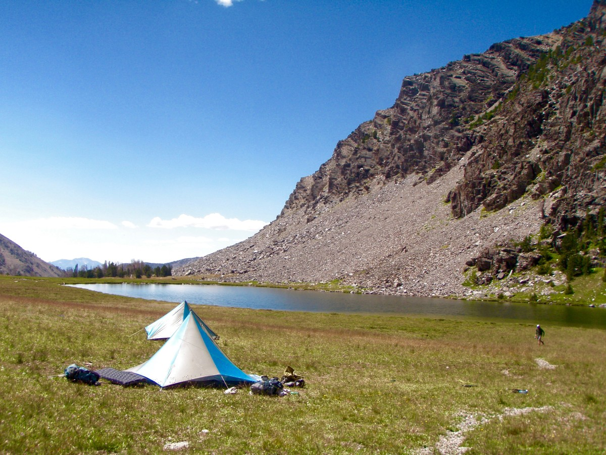 Tents on a lakeshore in the mountains