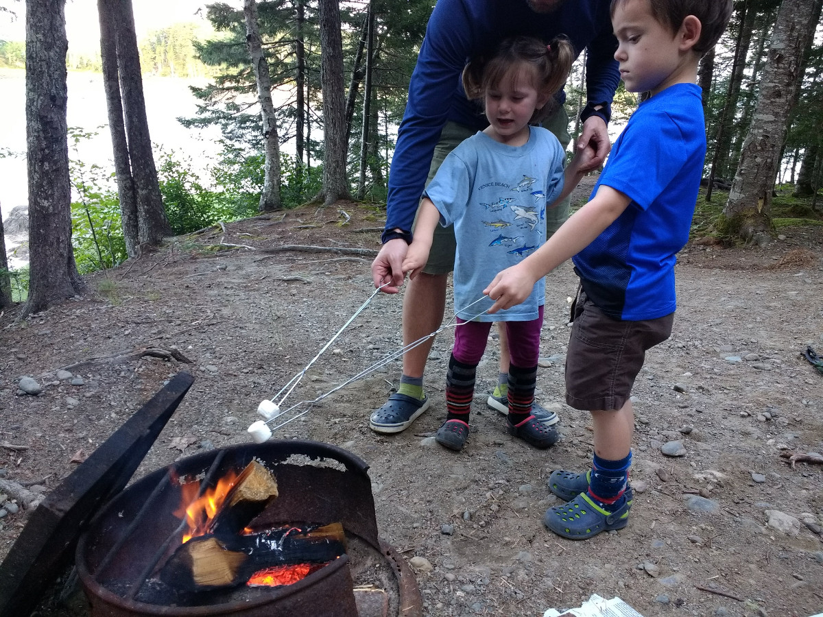 Kids roast marshmallows with help from parent
