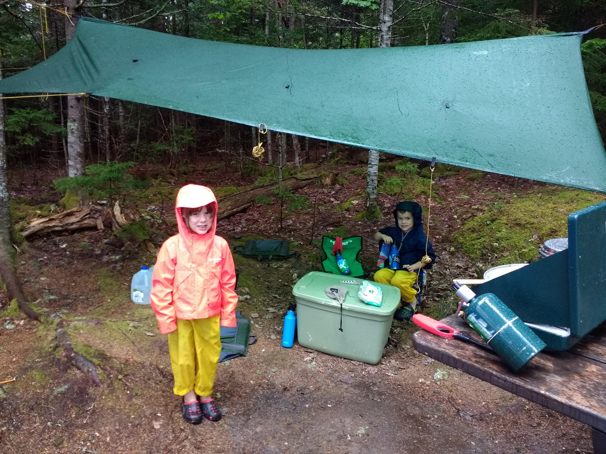 2 kids wearing raincoats under a tarp in camp