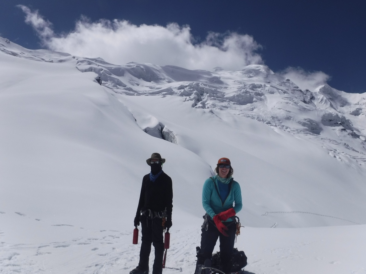 Two group members enjoy a rest and smile after a morning climb with mountains in the background