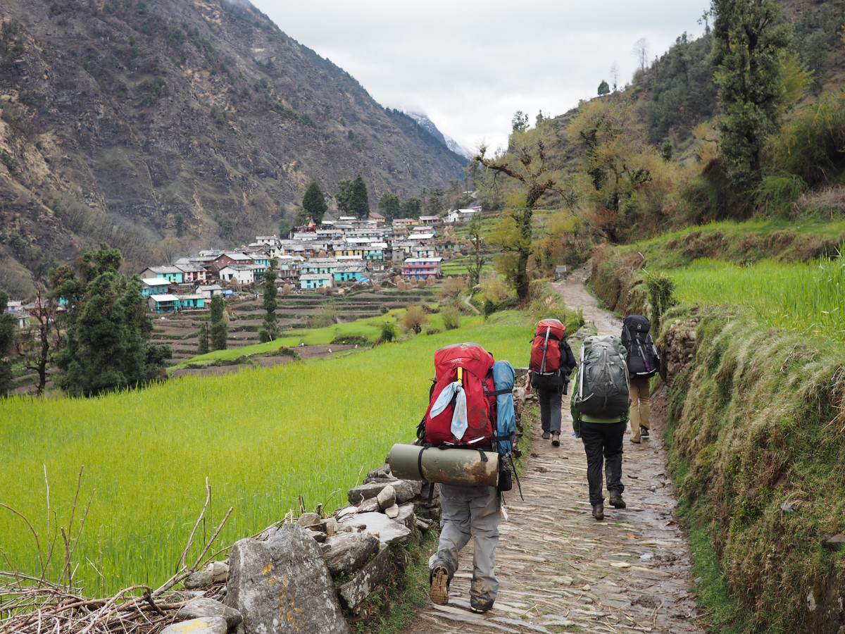 NOLS students hike wearing backpacks on a path in India with colorful village buildings in the background