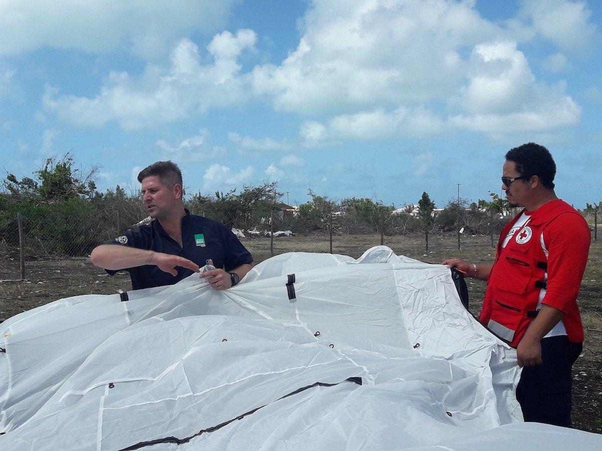 man wearing blue shirt helps man in Red Cross shirt set up white tent