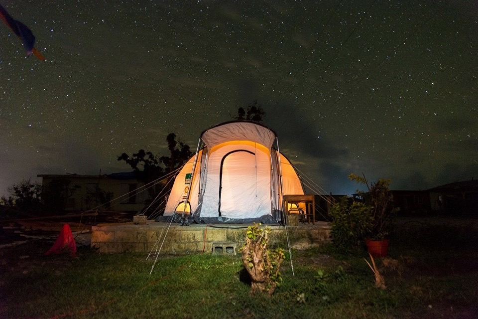orange and grey tent lit up with solar light on a starry night