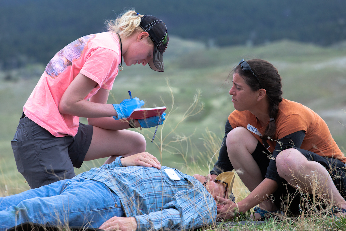two female wilderness medicine students practice caring for a patient in the outdoors