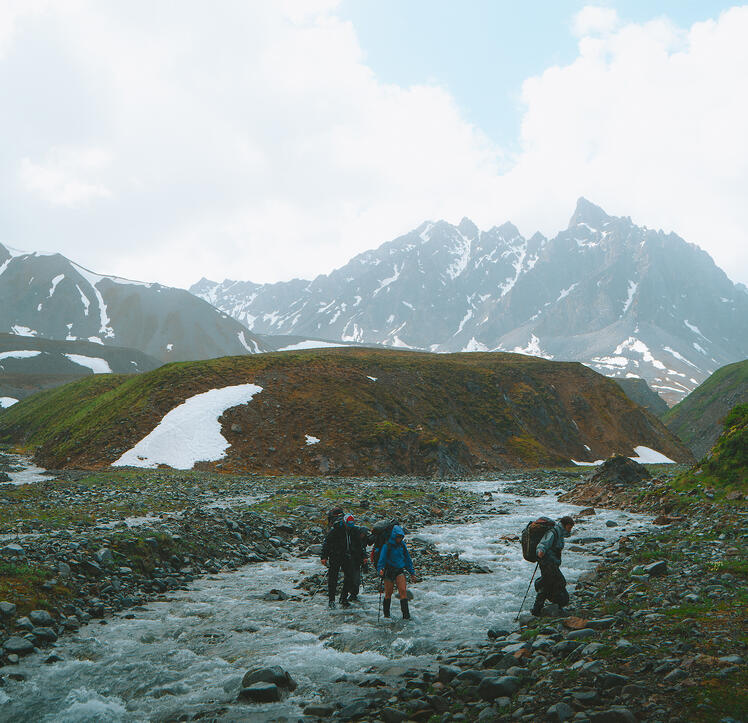 NOLS students cross a stream in mountains with patchy snow
